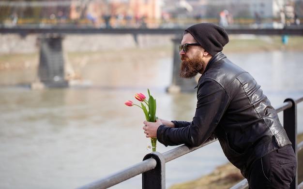 Brodaty mężczyzna w okularach przeciwsłonecznych z wąsami w czarnej ciepłej czapce i skórzanej kurtce trzyma bukiet czerwonych tulipanów, czekając na dziewczynę