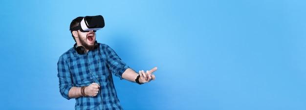 Brodaty mężczyzna w okularach wirtualnej rzeczywistości, emocjonalnie grający w strzelanki w vr na niebieskiej ścianie