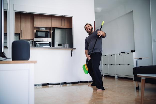 Brodaty mężczyzna w piżamie używa zamiatania, aby symulować gitarę, miotając podłogę swojego salonu, słuchając muzyki z inteligentnych głośników