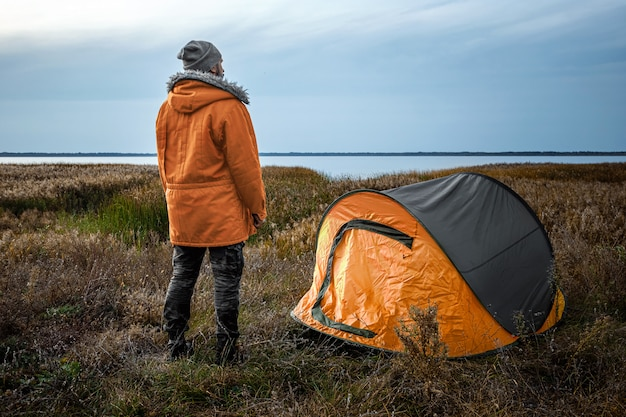 Brodaty mężczyzna w pobliżu namiotu kempingowego w pomarańczowej naturze i jeziorze. podróże, turystyka, camping.