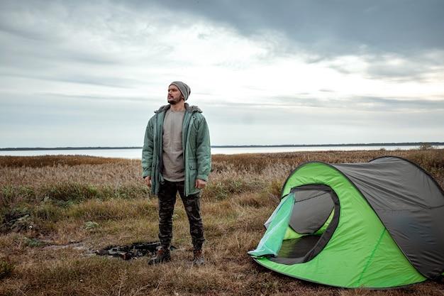 Brodaty mężczyzna w pobliżu namiotu kempingowego w zieleni i jeziora. podróże, turystyka, camping.