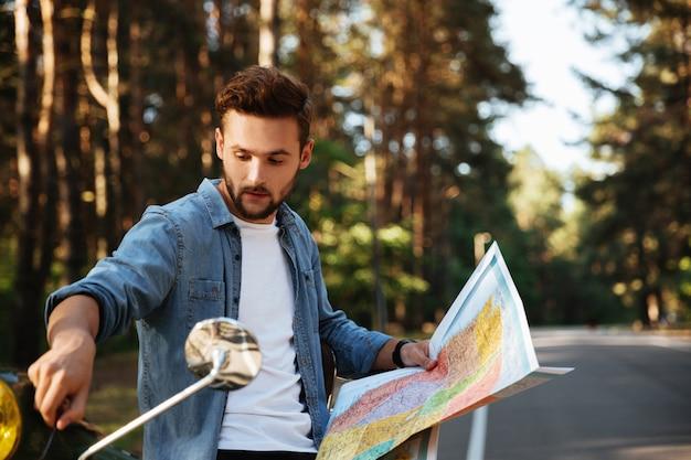 Brodaty mężczyzna w pobliżu skuter patrząc na mapę na zewnątrz.