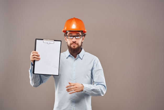 Brodaty mężczyzna w pomarańczowym kasku dokumenty inżyniera pracują