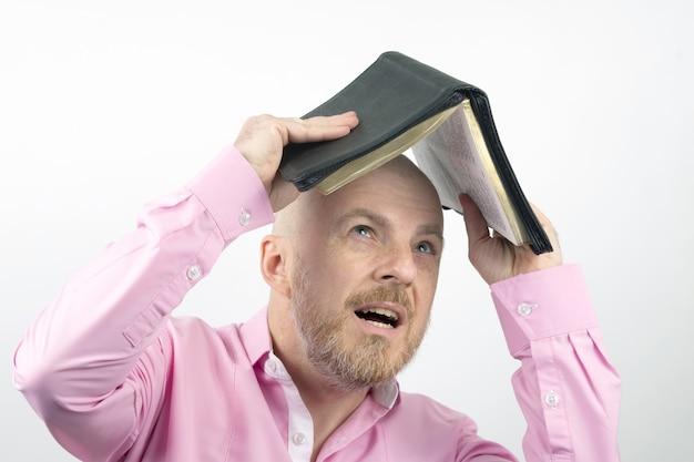 Brodaty mężczyzna w różowej koszuli chowa głowę pod otwartą biblią