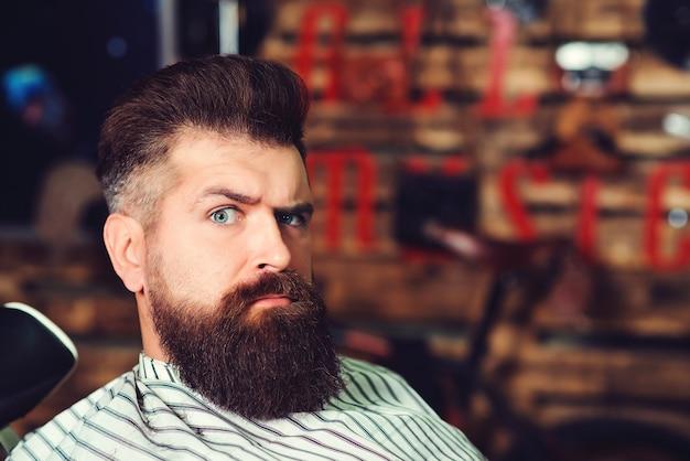 Brodaty mężczyzna w salonie fryzjerskim. męska fryzura, broda i wąsy. moda i męskie piękno.