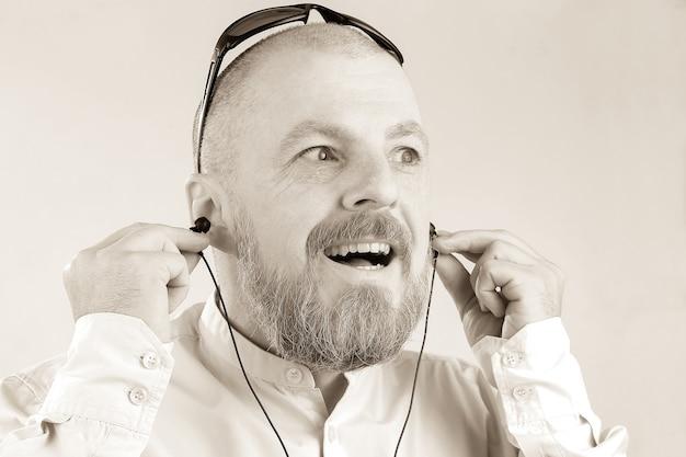 Brodaty mężczyzna w słuchawkach słucha muzyki. zainteresowania i hobby muzyczne. audio i technologia