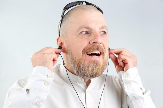 Brodaty mężczyzna w słuchawkach słucha muzyki