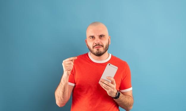 Brodaty mężczyzna w średnim wieku w czerwonej koszulce na niebieskim tle wskazuje ręką na telefon. zadzwoń. odosobniony.