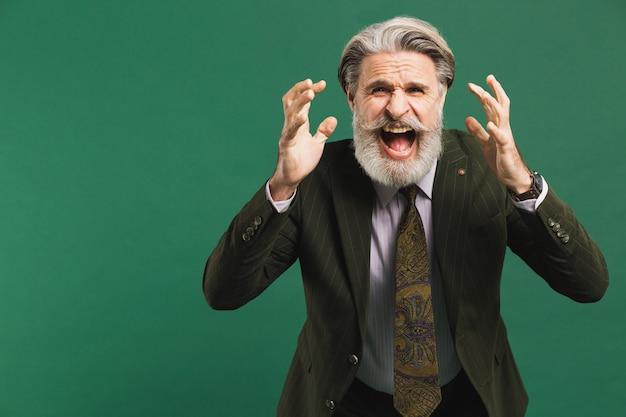 Brodaty mężczyzna w średnim wieku w garniturze głośno krzyczy i opiera pięści na zielonej ścianie