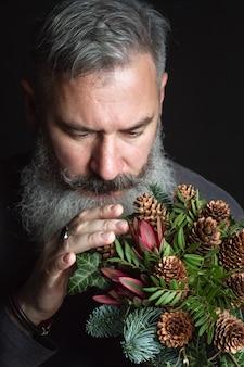 Brodaty mężczyzna w średnim wieku z zimowym bukietem gałązek jodłowych nobil, szyszek, pistacji, leucodendronu i bluszczu, koncepcja zimowego prezentu