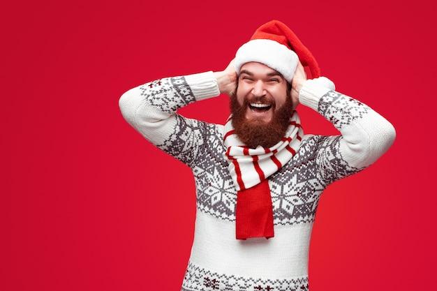 Brodaty mężczyzna w świątecznym kapeluszu śmiejący się i zszokowany