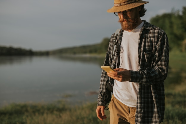 Brodaty mężczyzna w swobodnym stroju sprawdzającym lokalizację gps na smartfonie