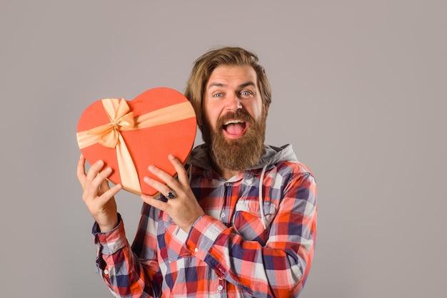 Brodaty mężczyzna w swobodnym stylu trzyma pudełko upominkowe mężczyzna trzyma pudełko upominkowe walentynkowe w kształcie serca czas dla