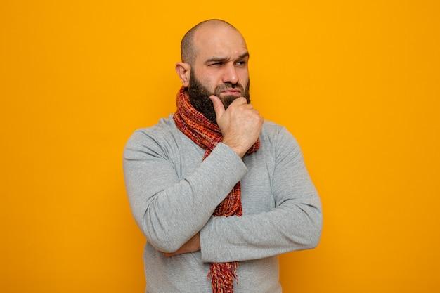 Brodaty mężczyzna w szarej bluzie z szalikiem na szyi patrzący w bok z zamyślonym wyrazem twarzy myślący