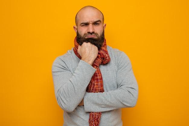 Brodaty mężczyzna w szarej bluzie z szalikiem na szyi, patrzący z ręką na brodzie, myślący