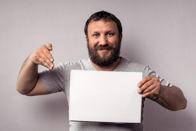Brodaty mężczyzna w szarej koszulce pokazujący pusty biały plakat trzymający i wskazujący ręką na białej karcie