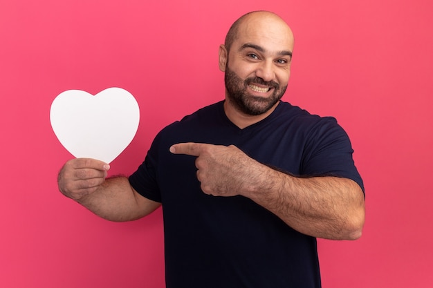 Brodaty mężczyzna w t-shirt trzyma kartonowe serce wskazując palcem wskazującym na niego uśmiechnięty z radosną twarzą stojącą nad różową ścianą