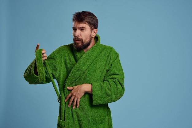 Brodaty mężczyzna w zielonej szacie z paskiem na niebieskim tle przycięty widok emocji. wysokiej jakości zdjęcie