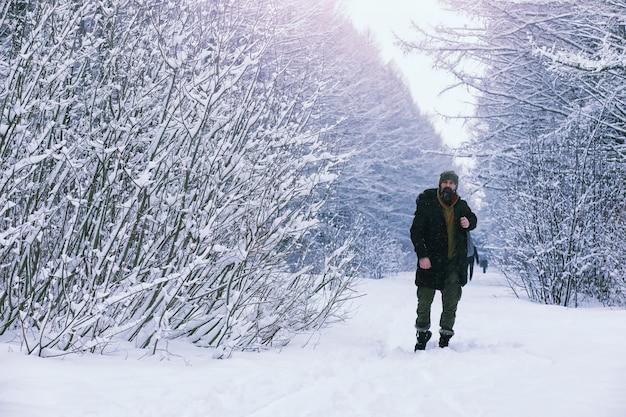 Brodaty mężczyzna w zimowym lesie. atrakcyjny szczęśliwy młody człowiek z brodą spacer w parku.