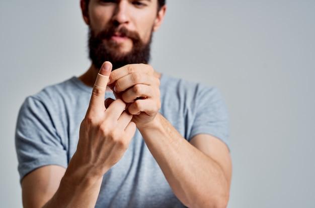 Brodaty mężczyzna wbija sobie palec w plaster leczący problemy zdrowotne