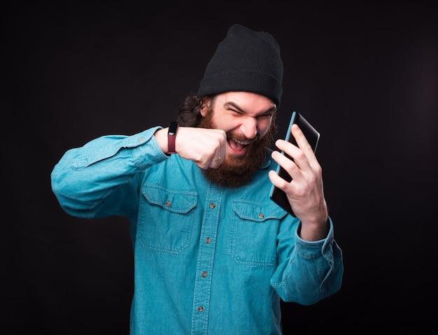 Brodaty mężczyzna wrzeszczy i bucha telefonem, który trzyma w pobliżu czarnej ściany