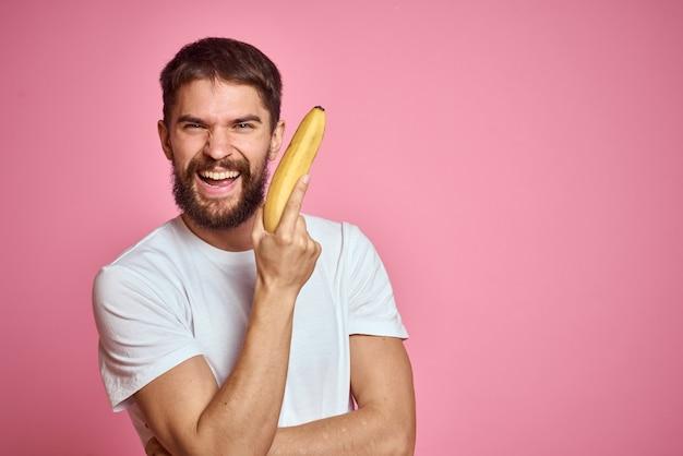 Brodaty mężczyzna z bananem w dłoni na modelu emocji zabawy różowy przestrzeni