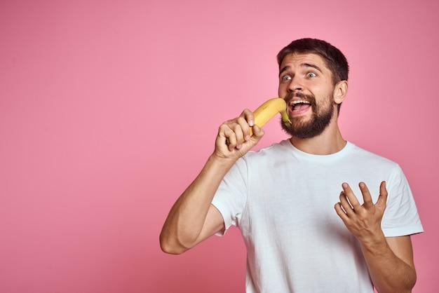 Brodaty mężczyzna z bananem w dłoni na różowo