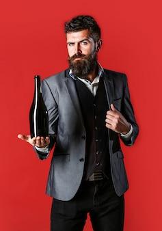 Brodaty mężczyzna z butelką szampana i szkła. stylowy mężczyzna w smokingu, garniturze, marynarce. mężczyzna trzyma butelkę z szampanem, winem. osoba trzyma w dłoni butelkę czerwonego wina.