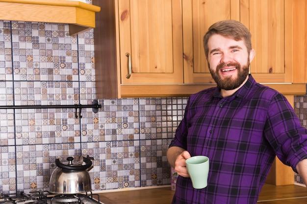 Brodaty mężczyzna z czajnikiem herbaty na śniadanie w domowej kuchni