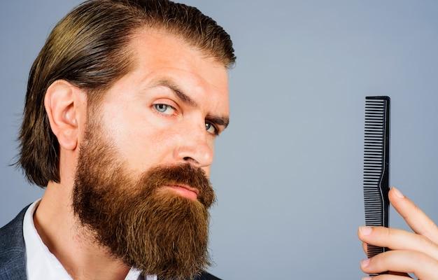 Brodaty mężczyzna z grzebieniem fryzjerskim, fryzjer i fryzjer, salon dla mężczyzn, profesjonalna pielęgnacja brody.