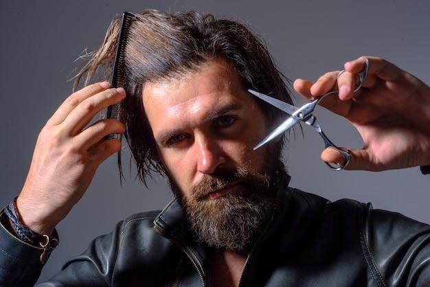 Brodaty mężczyzna z grzebieniem fryzjerskim i nożyczkami salon fryzjerski dla mężczyzn profesjonalna pielęgnacja brody