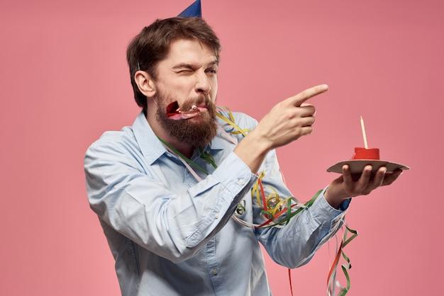 Brodaty mężczyzna z językiem ciasta na różowym tle przycięty widok i niebieską czapkę na głowie. wysokiej jakości zdjęcie
