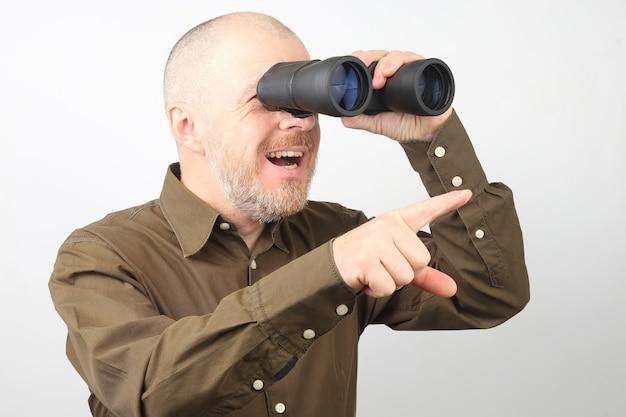 Brodaty mężczyzna z lornetką w dłoniach patrzy radośnie w dal