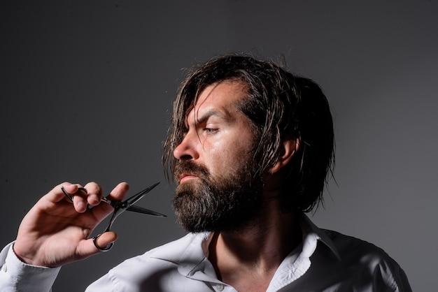 Brodaty mężczyzna z nożyczkami fryzjerskimi profesjonalna pielęgnacja brody fryzjer razor salon fryzjerski dla mężczyzn