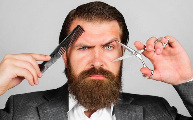 Brodaty mężczyzna z nożyczkami i grzebieniem. fryzjer z narzędziami fryzjerskimi. mężczyzna stylista w salonie fryzjerskim. salon kosmetyczny i fryzjerski.