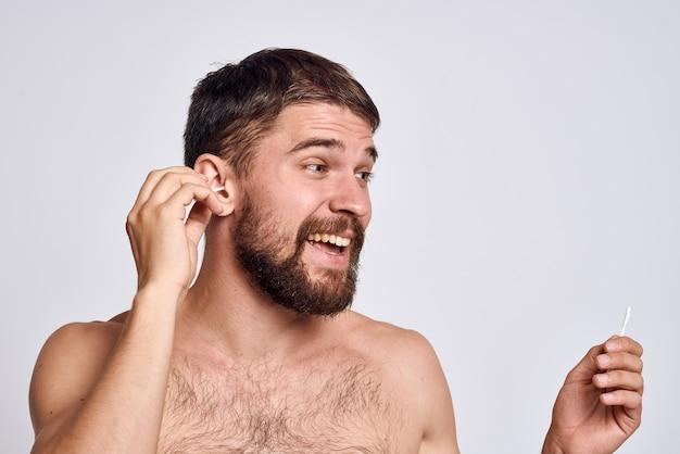Brodaty mężczyzna z odkrytymi ramionami waciki higieniczne do pielęgnacji ciała.
