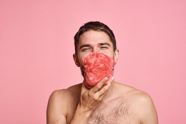 Brodaty mężczyzna z odkrytymi ramionami z myjką z czystą skórą w łazience. wysokiej jakości zdjęcie