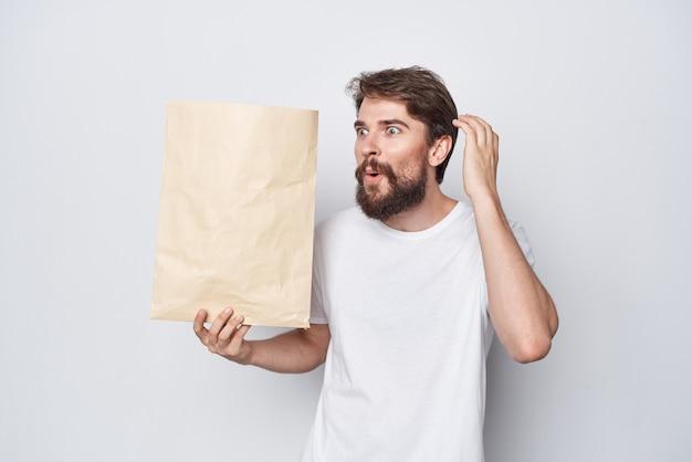 Brodaty mężczyzna z pakietem rzemieślniczym w rękach zakupy emocje jasne tło
