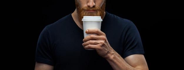 Brodaty mężczyzna z papierowym kubkiem kawy