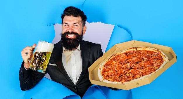 Brodaty mężczyzna z pyszną pizzą i piwem patrząc przez dziurę papieru. ciesz się pyszną pizzą i zimnym piwem.