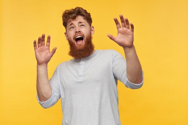 Brodaty mężczyzna z rudymi włosami, patrzący w górę, z szeroko otwartymi ustami i uniesionymi rękami, czuje się o coś przerażony