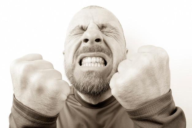 Brodaty mężczyzna z silnymi emocjami i zbliżeniem zaciśniętych pięści na białym tle. agresja i nerwowość. stres i szaleństwo