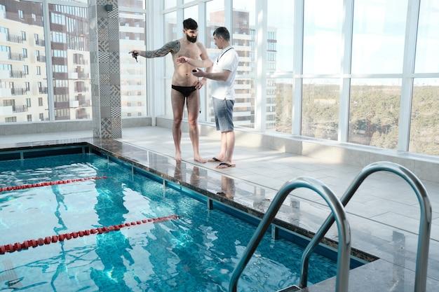 Brodaty mężczyzna z tatuażem wskazującym na pas podczas omawiania odległości pływania z trenerem w basenie