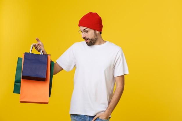Brodaty mężczyzna z torba na zakupy z szczęśliwym uczuciem odizolowywającym na żółtym bacground