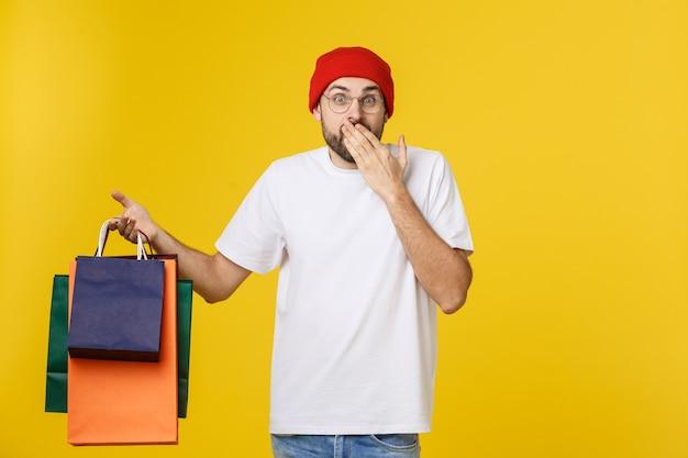 Brodaty mężczyzna z torby na zakupy z szczęśliwym uczuciem odizolowanym na żółto.