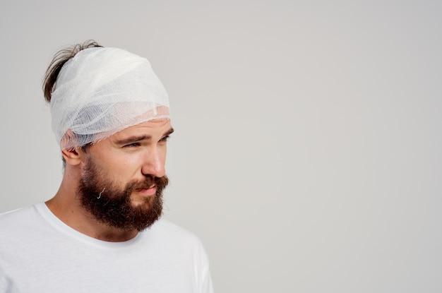 Brodaty mężczyzna z zabandażowaną głową i krwią dłoni