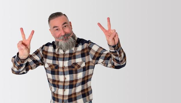 Brodaty mężczyzna z zabawnym wyrazem twarzy i stylu retro, podnosząc ręce i umieszczając je palcami robiąc znak zwycięstwa