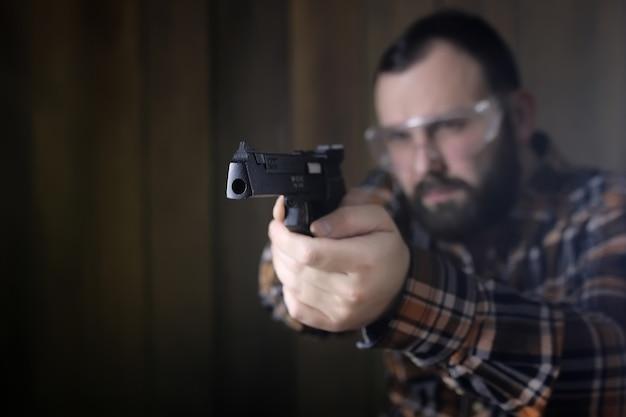 Brodaty mężczyzna z założonymi goglami ochronnymi i treningiem słuchu w strzelaniu z pistoletu