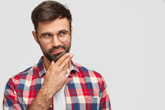 Brodaty mężczyzna z zamyślonym wyrazem twarzy, trzyma brodę, skupiony na boku, kontempluje sytuację życiową, ubrany w swobodny strój