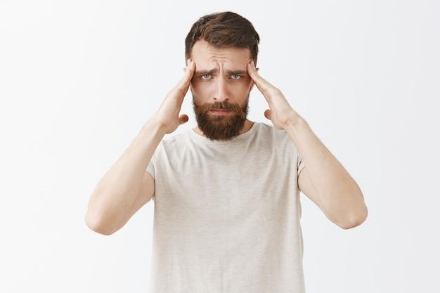 Brodaty mężczyzna z zawrotami głowy, pozujący przy białej ścianie